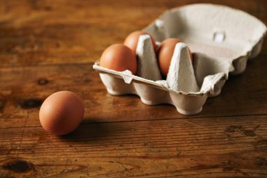 Close up shot of an open recyclable egg carton with 3 eggs inside and one egg next to it on a brown grainy wooden table Ecological healthy food from bio farms.
